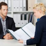 Blonde Interviewer Reviewing Resume in Front of Interviewee