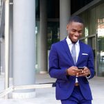 African Business Man Smiling at Smartphone