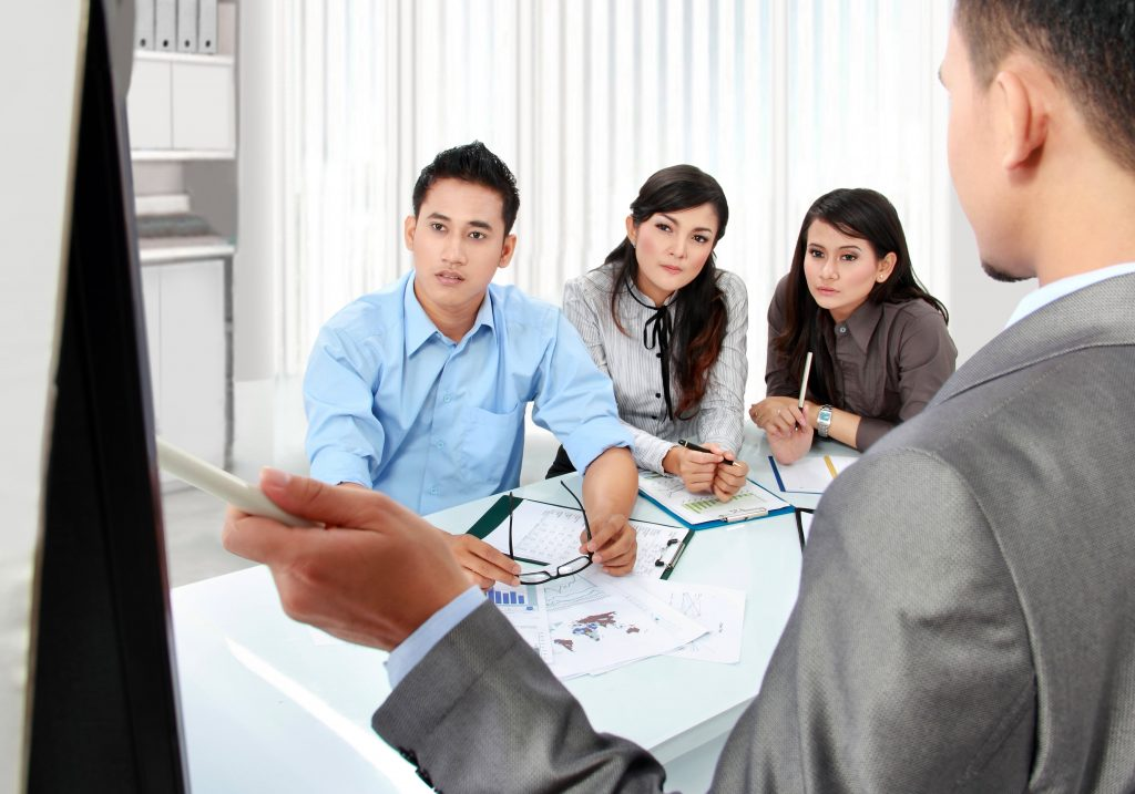 Three employees in a conference room listening to a training presentation.