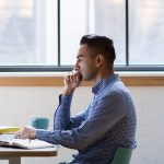 Young man sitting at a desk contemplating how implement hr in a startup