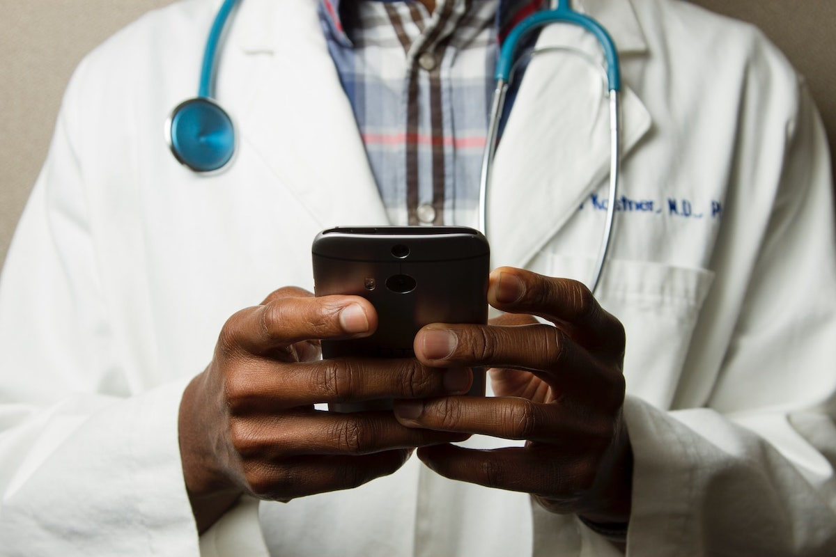 doctor using cell phone to communicate with patients during coronavirus