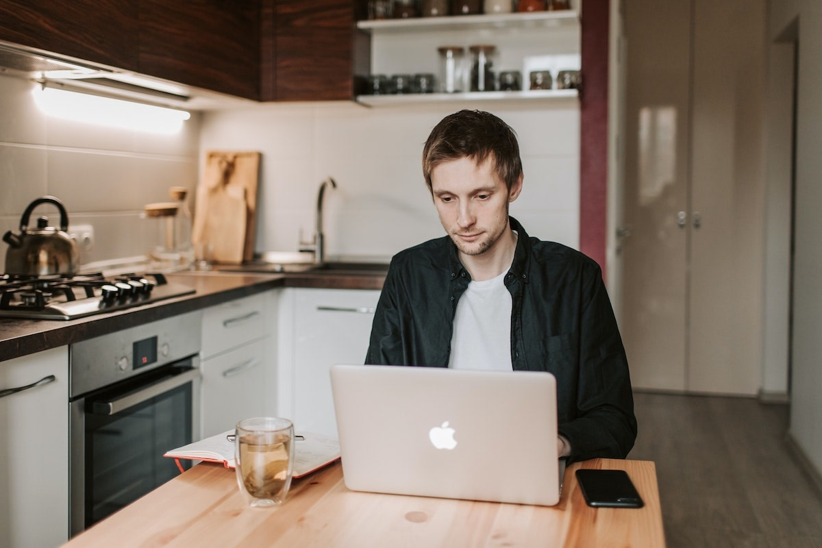 man working remotely with laptop from kitchen counter
