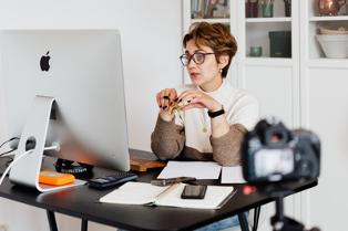 elegant lady wearing glasses hosting webinar