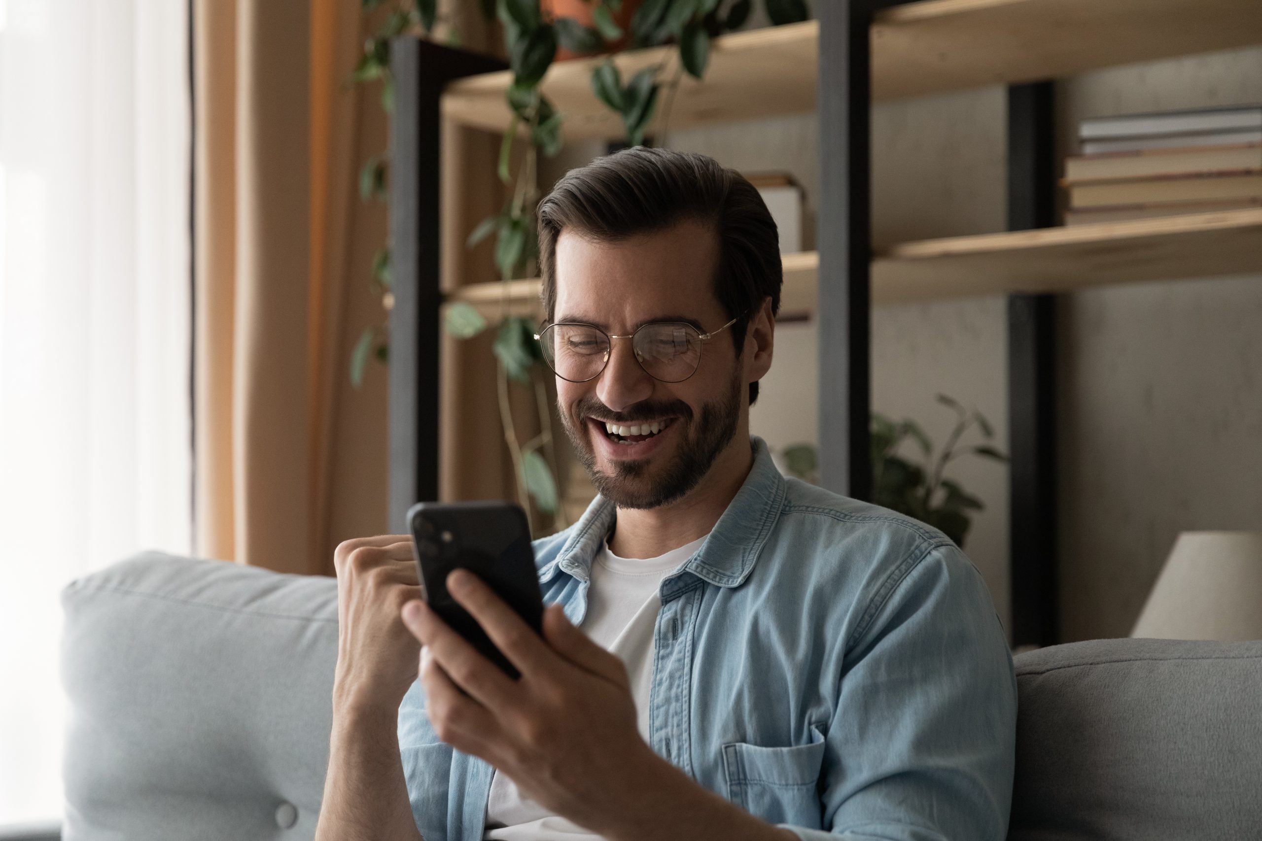 overjoyed man with glasses who gets phone job interview request